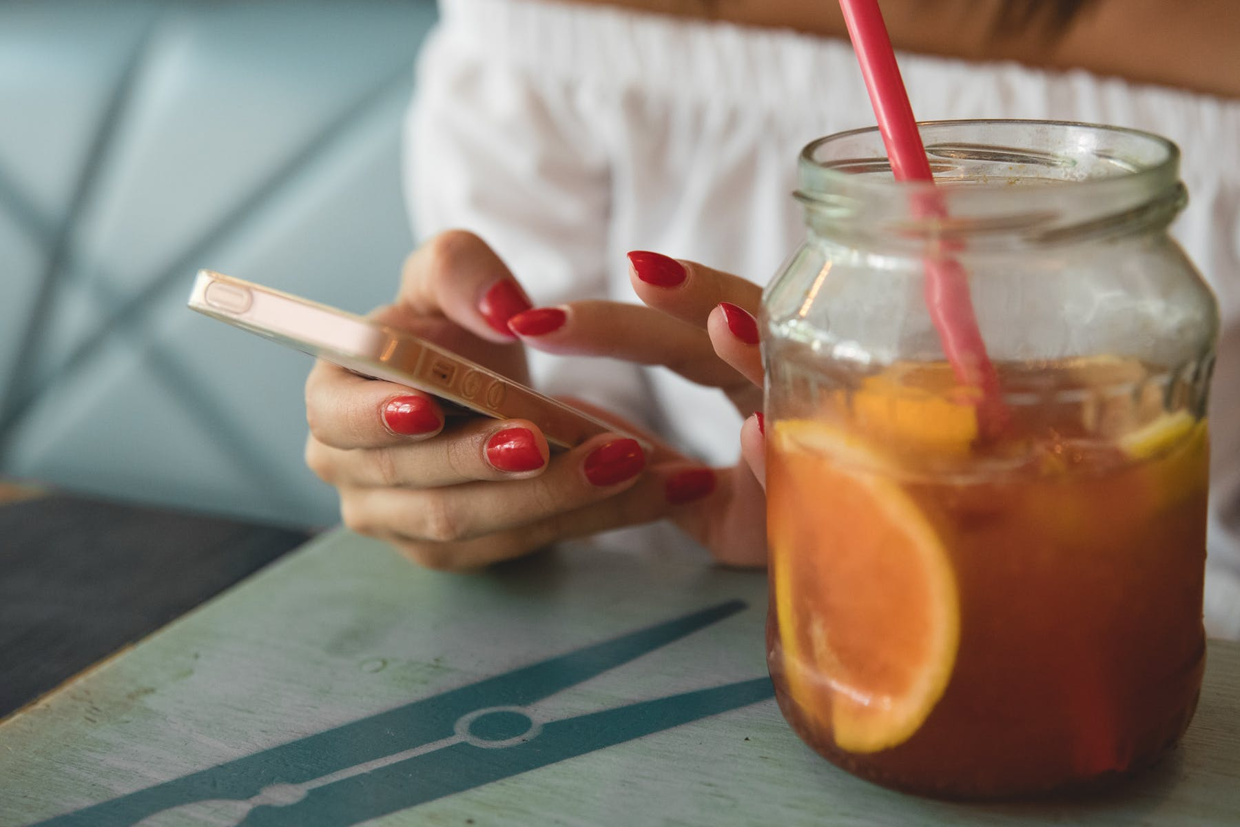 hand with cellphone next to a glass iced tea