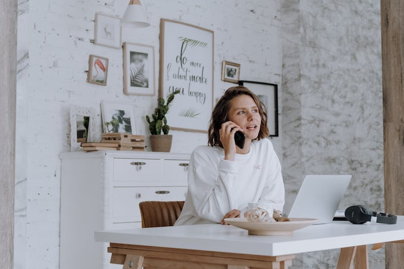 girl on phone in front of computer