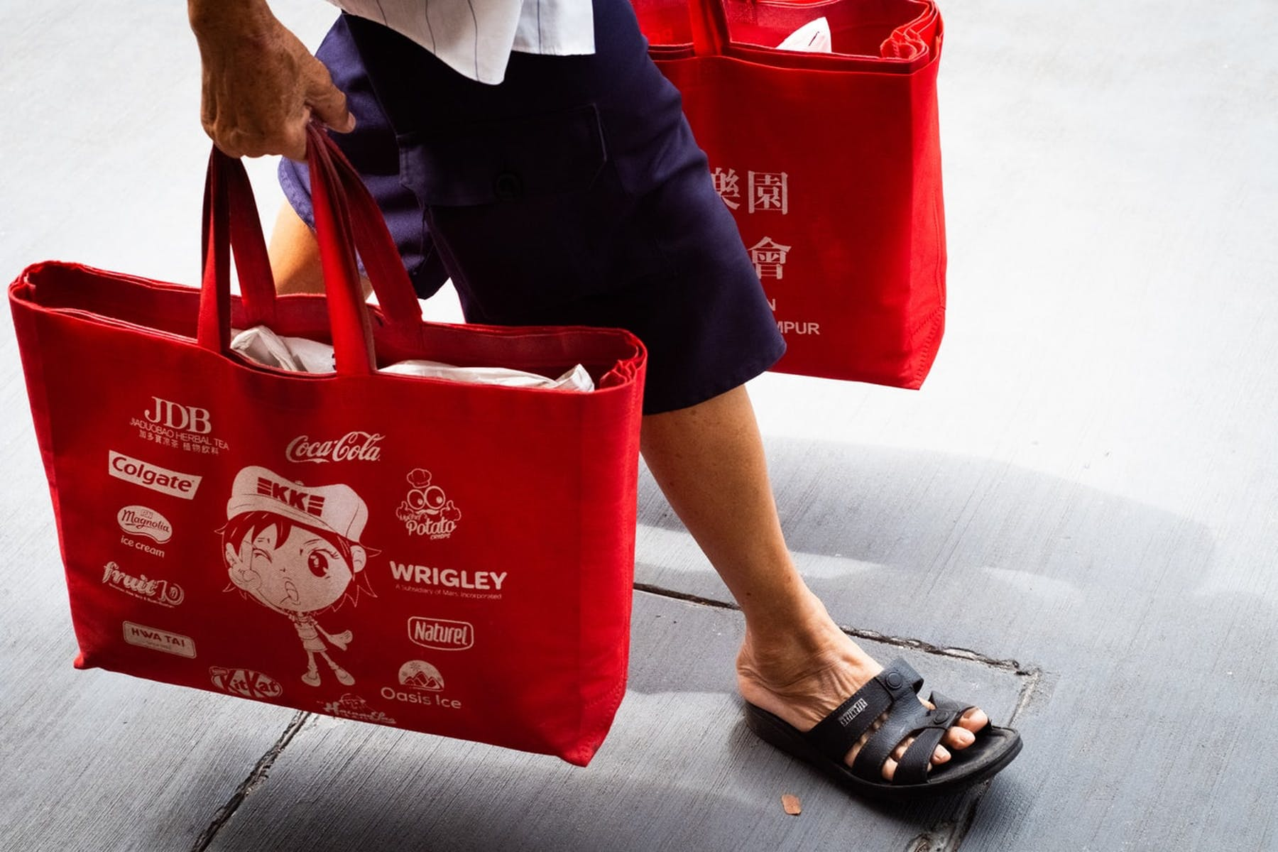 man walking with red shopping bags