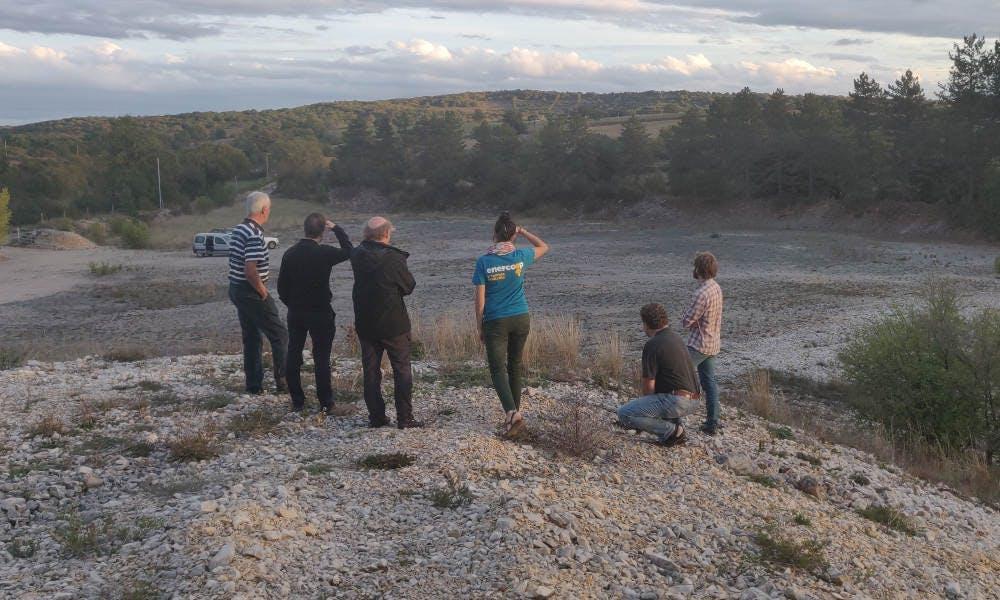 Personnes observant le terrain du futur parc solaire de Combel-Rimat à Blars, par Enercoop Midi-Pyrénées