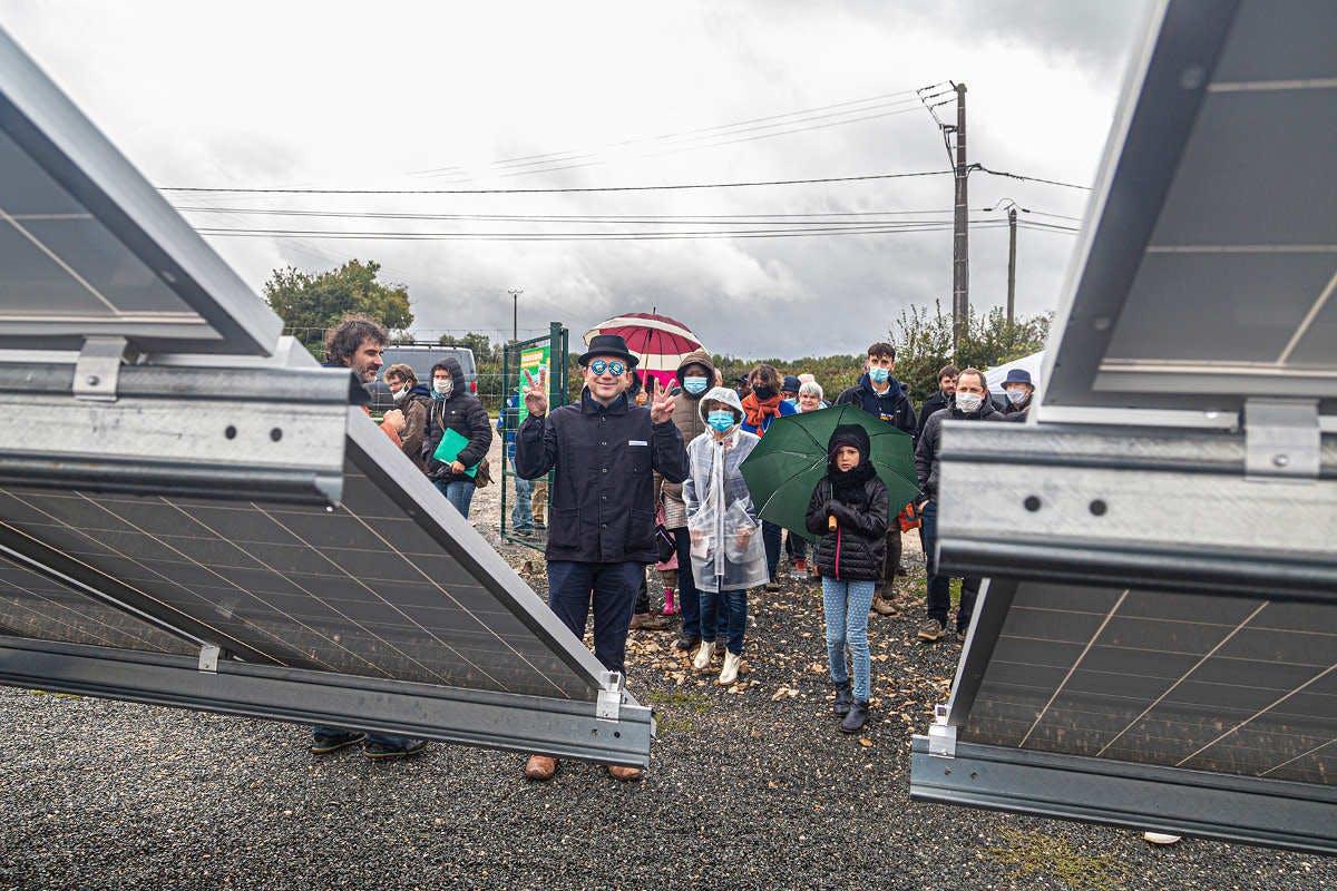 Foule visitant le parc solaire coopérative d'Enercoop Midi-Pyrénées à Montfaucon (Lot), dont un clow