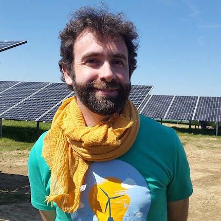 Homme souriant devant des panneaux solaires