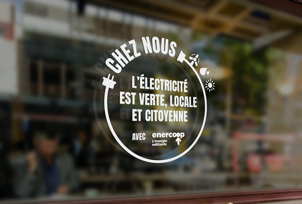 """Sticker collé sur une vitrine """"chez nous l'électricité est verte, locale et citoyenne"""""""