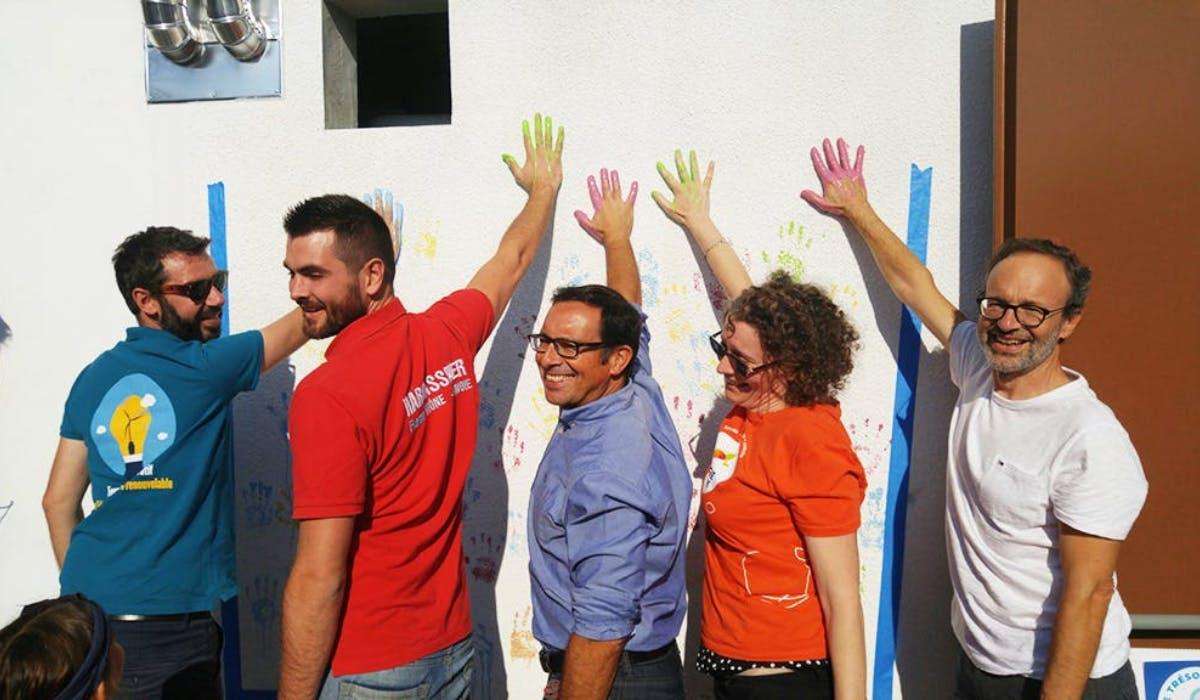Membres de la société citoyenne touchant le mur avec leurs mains remplies de peinture