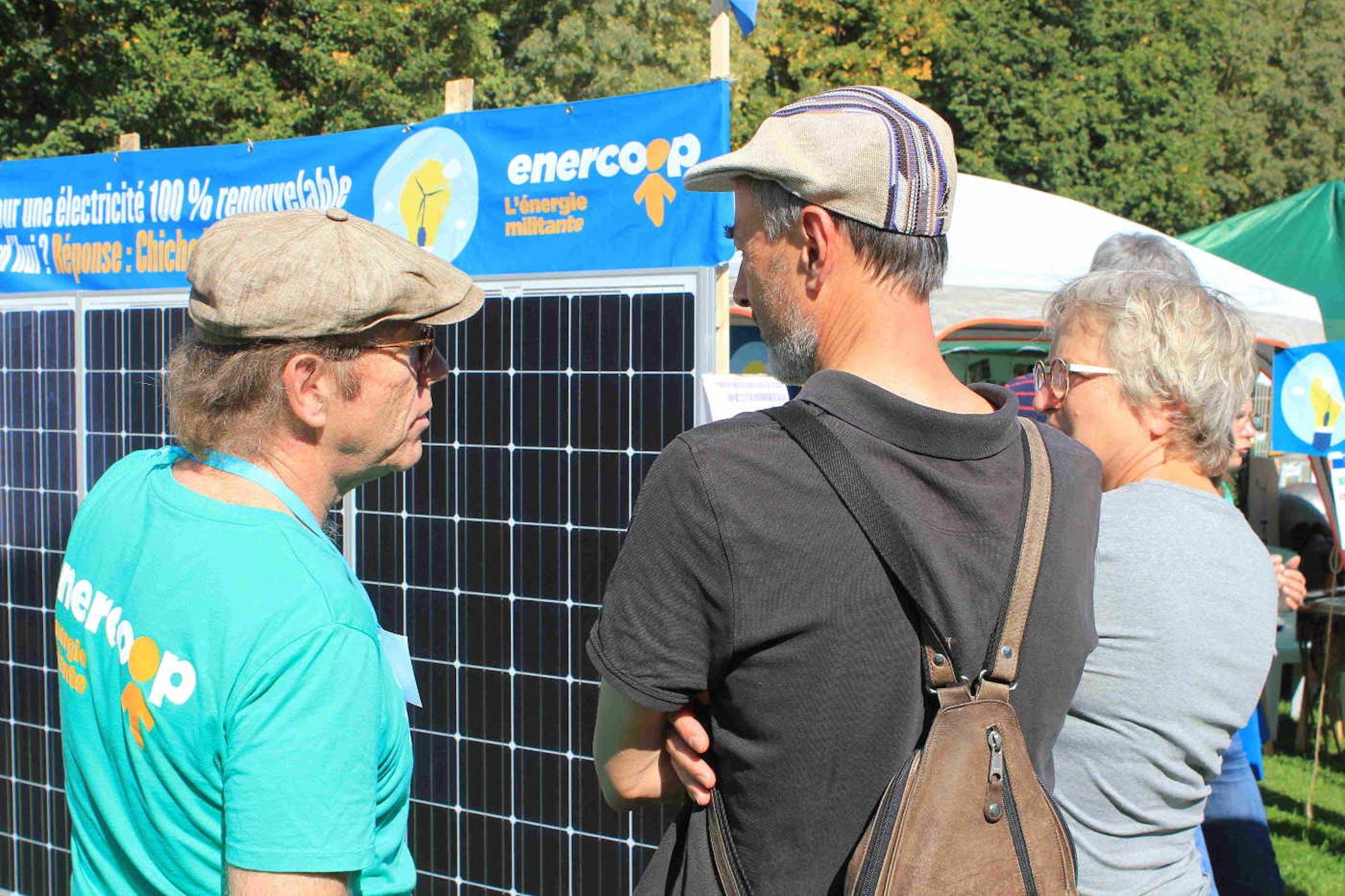 3 personnes discutent devant un panneau photovoltaïque Enercoop