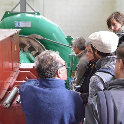 un troupe de personne autour d'une turbine de barrage
