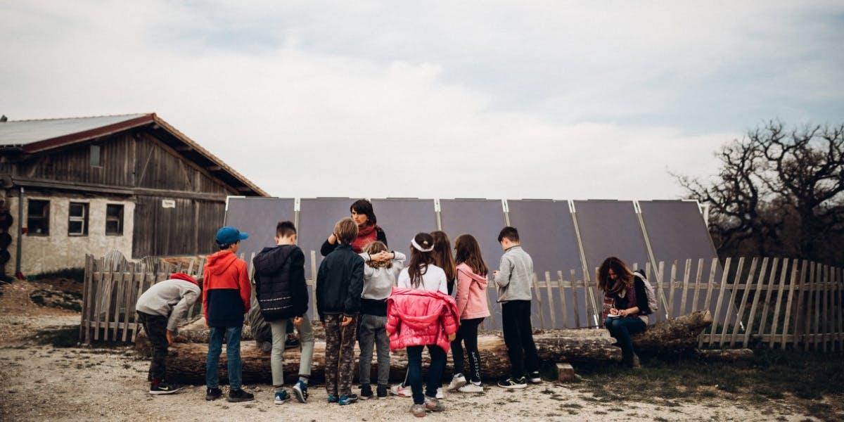 Enfants de dos écoutant une guide lors d'une classe découverte aux Amanins