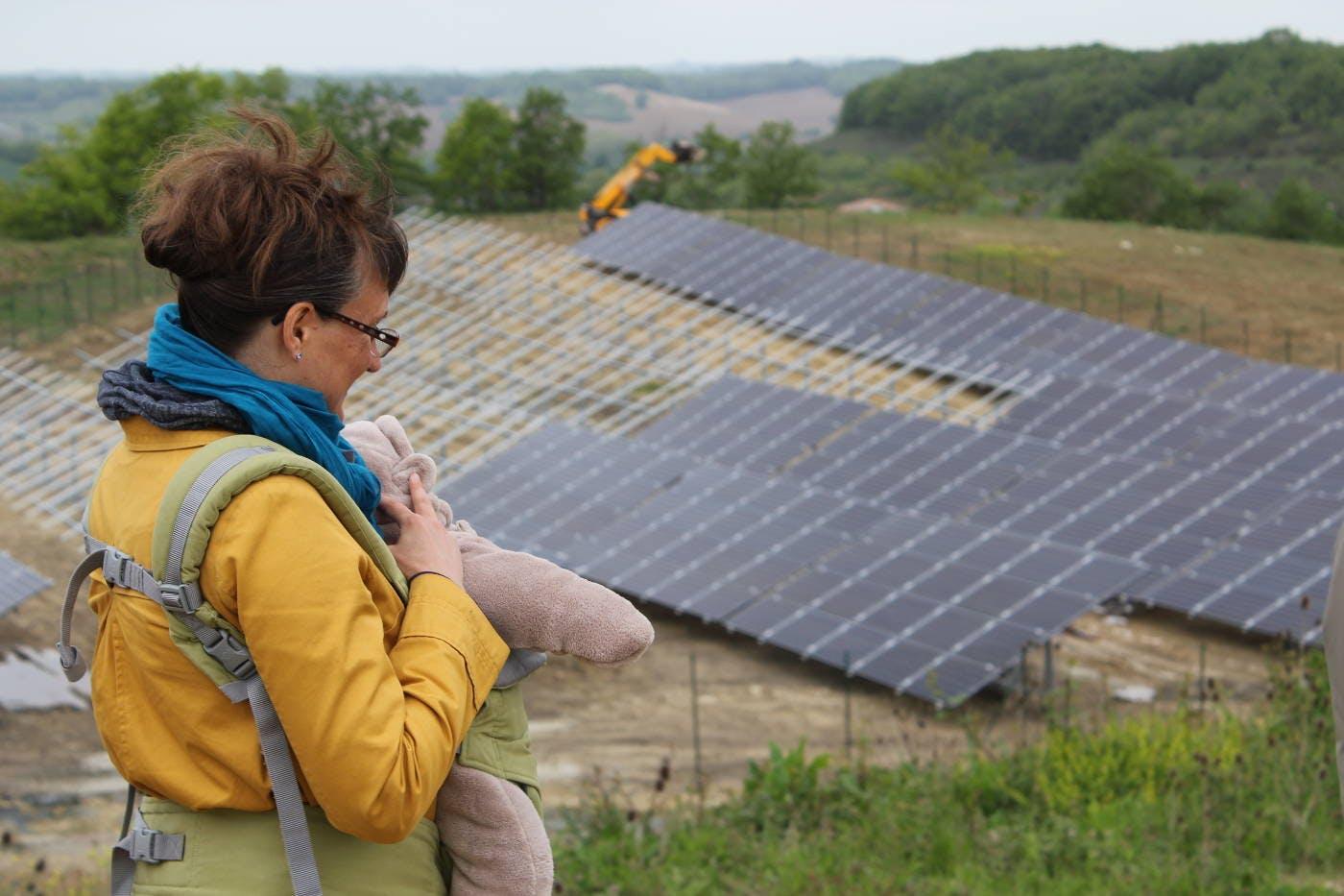 Femme portant un bébé devant un parc solaire d'Enercoop Midi-Pyrénées en construction