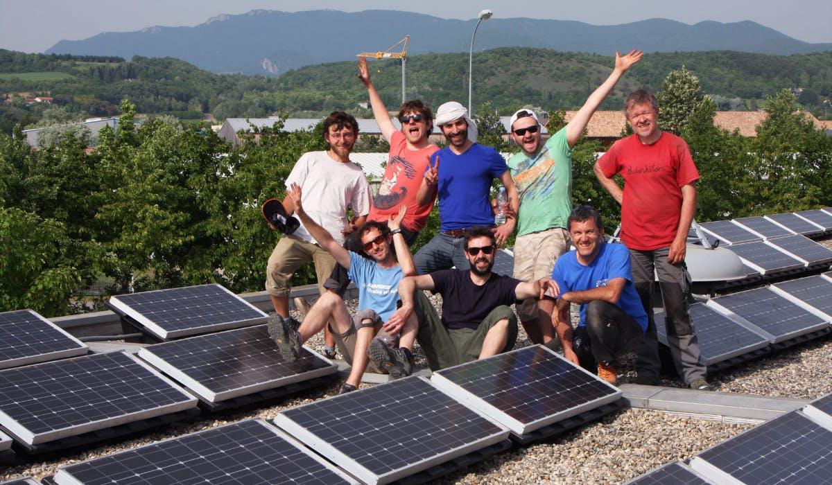 Acteurs du projet Soleil Marguerite posant en groupe devant les panneaux solaires