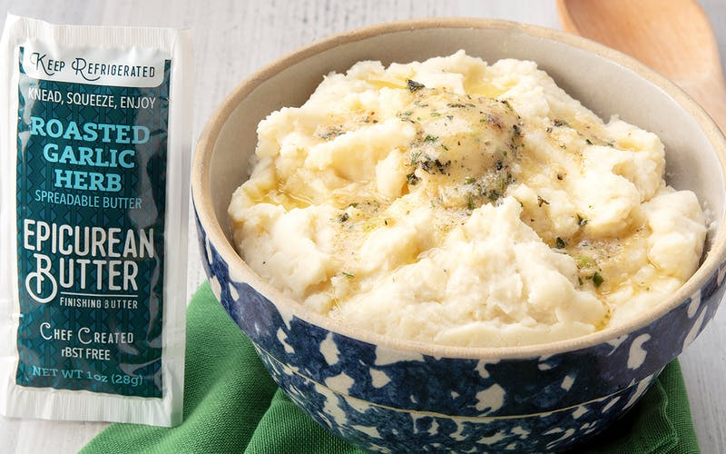 Bowl of mashed potatoes and 1oz squeeze packet of Epicurean Roasted Garlic Herb Butter.