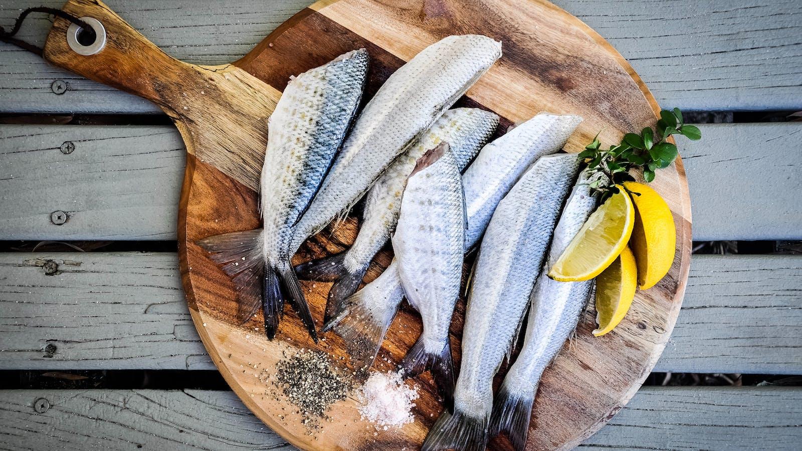 Petits poissons posés sur une planche en bois avec du citron