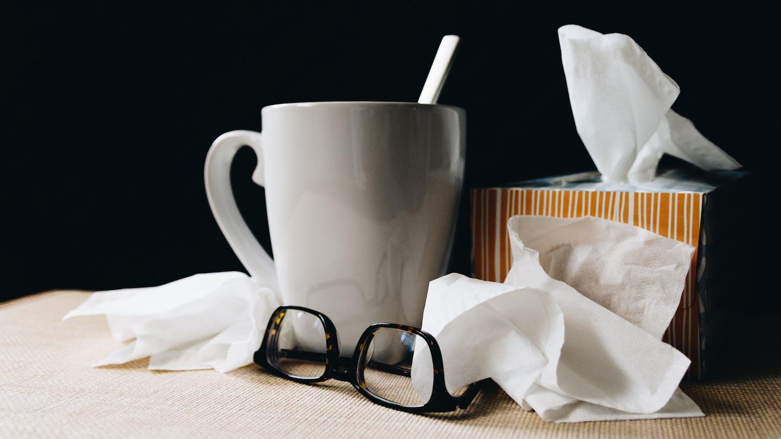 Une tasse de café, une boîte de mouchoirs utilisés et une paire de lunettes à l'envers