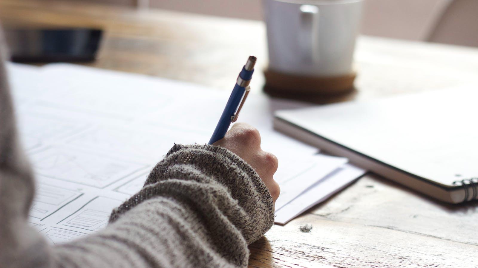 femme tient un stylo accoudée sur un bureau
