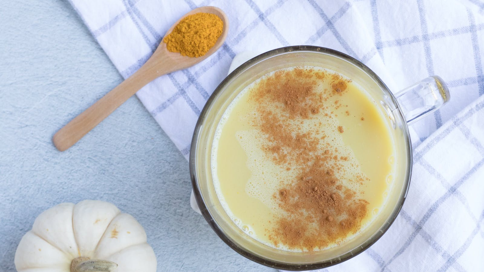Photo d'un golden milk dans une tasse posée sur un torchon à carreaux