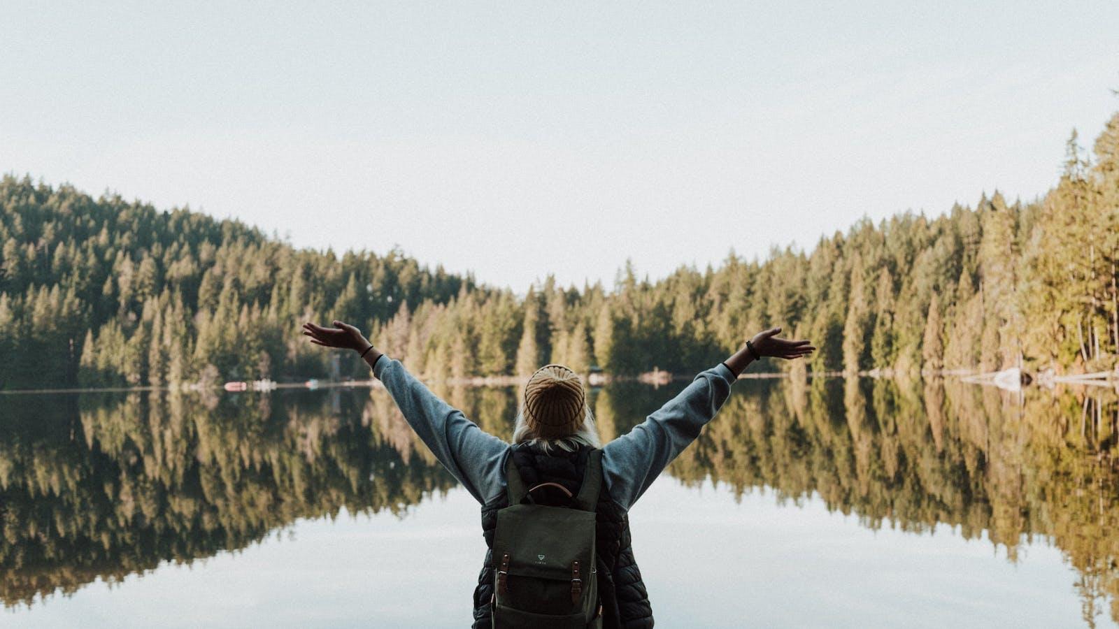 Photo d'une femme, les bras levés vers le haut face à un lac