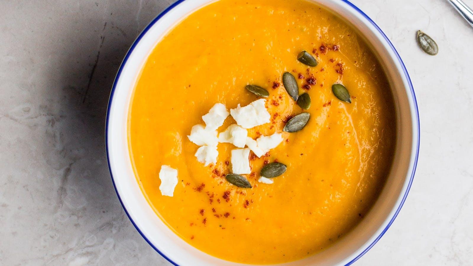 Velouté orange avec des morceaux de fromage et des graines de courge