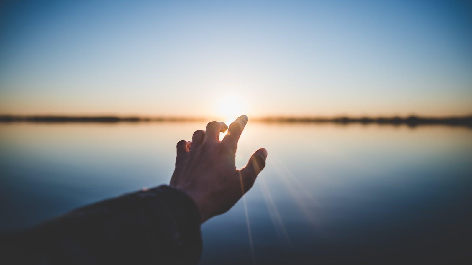 Main qui touche le coucher du soleil