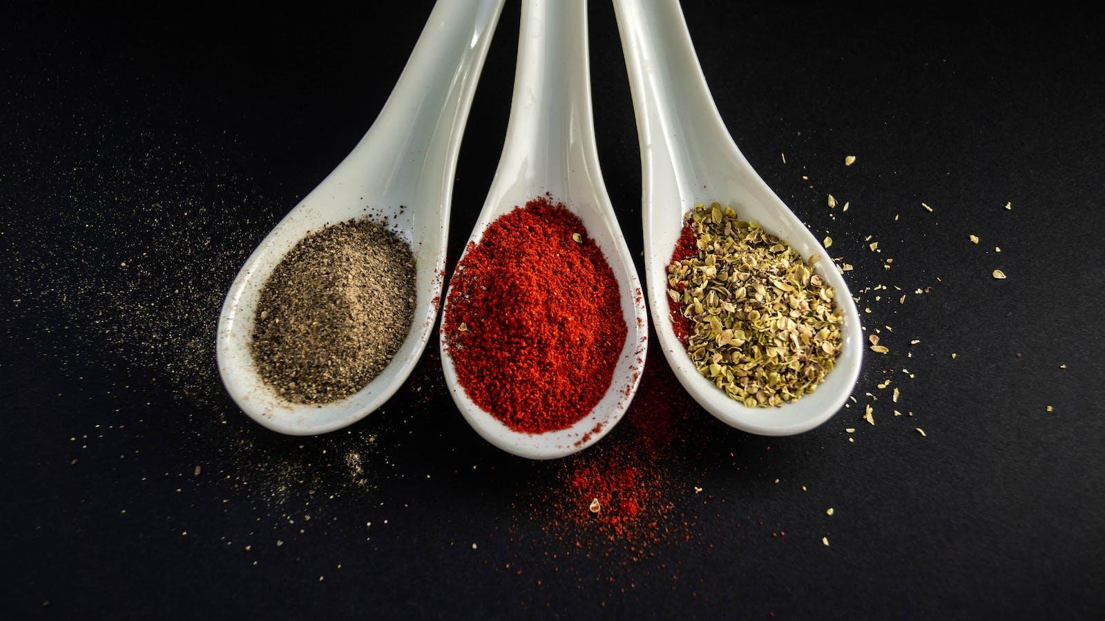 Des épices très colorées sur des cuillères blanches