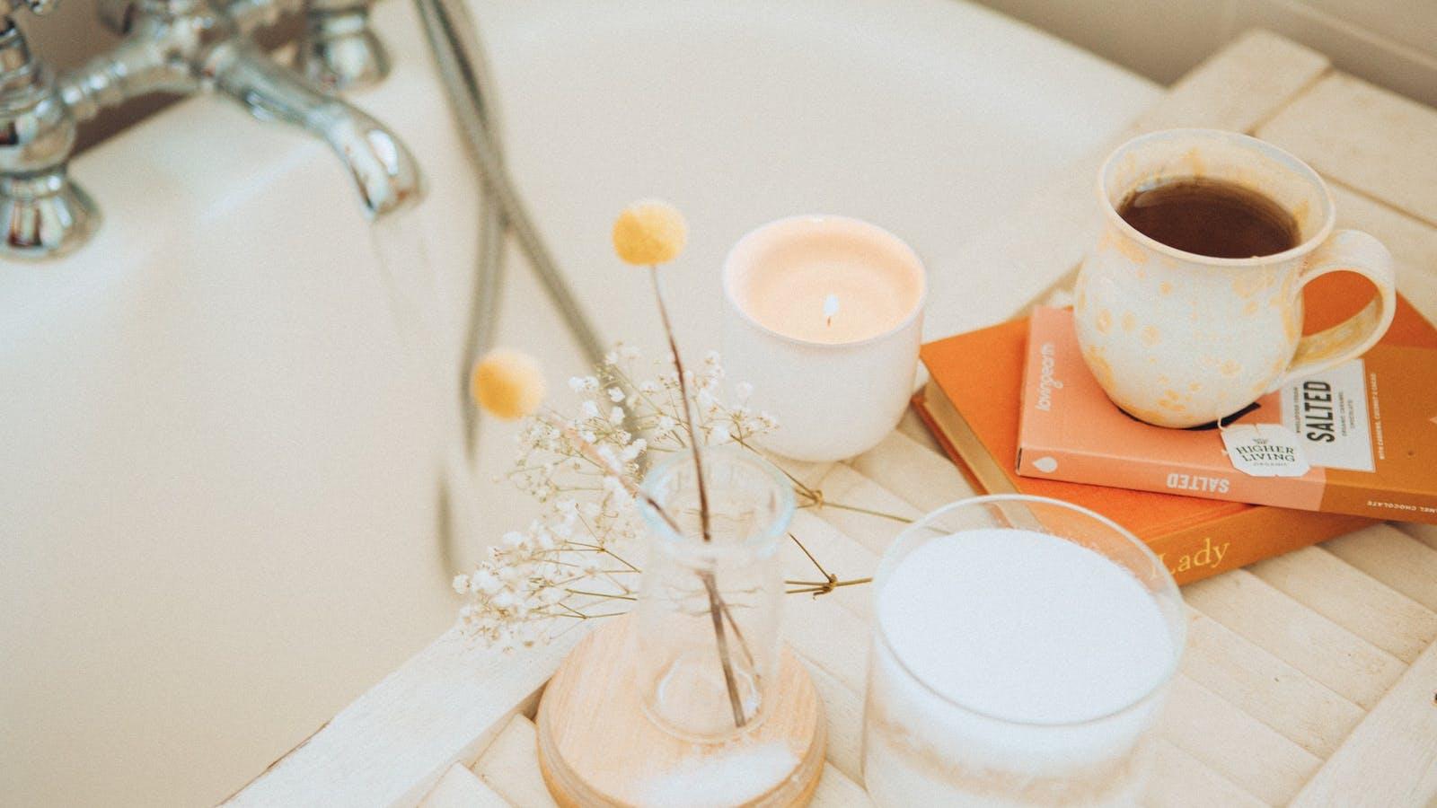 Photo d'un bain avec des livres, des fleurs et une tasse de thé