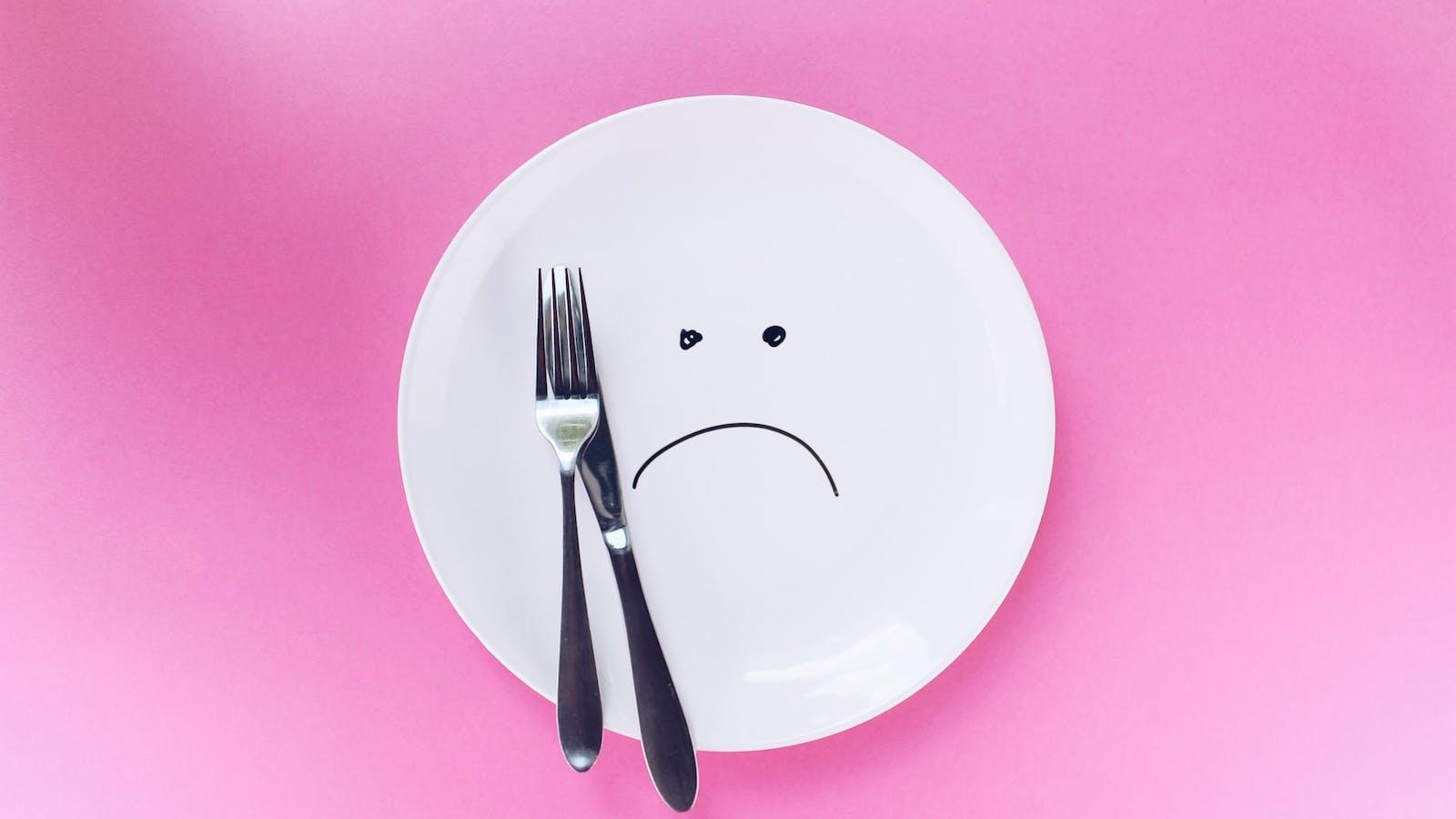 Assiette blanche sur fond rose
