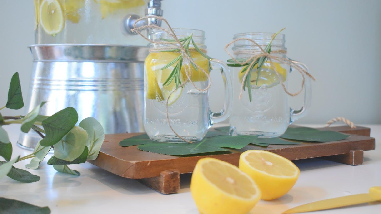 Deux verres contenant de l'eau avec citrons coupés en deux