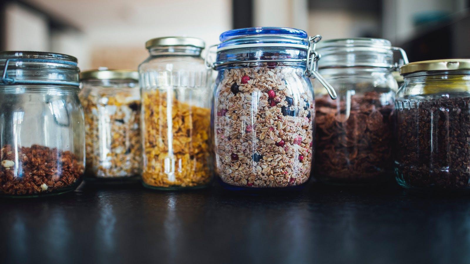 Céréales dans des pots en verre sur un plan de travail noir