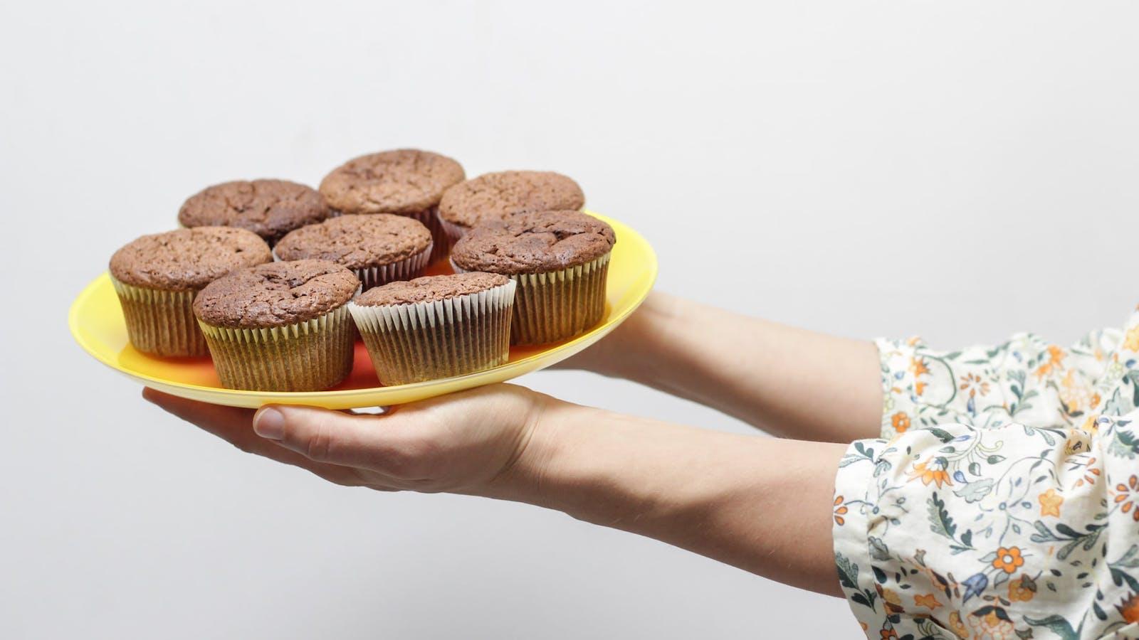 Bras tendus présentant une assiette de 8 muffins au chocolat