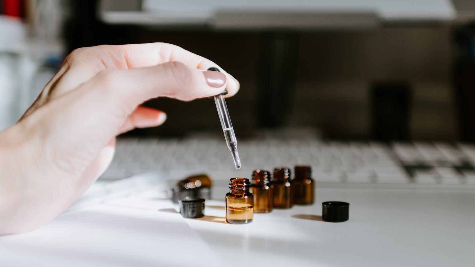Photo d'huiles essentielles dans des pots en verre avec une main qui tient une pipette