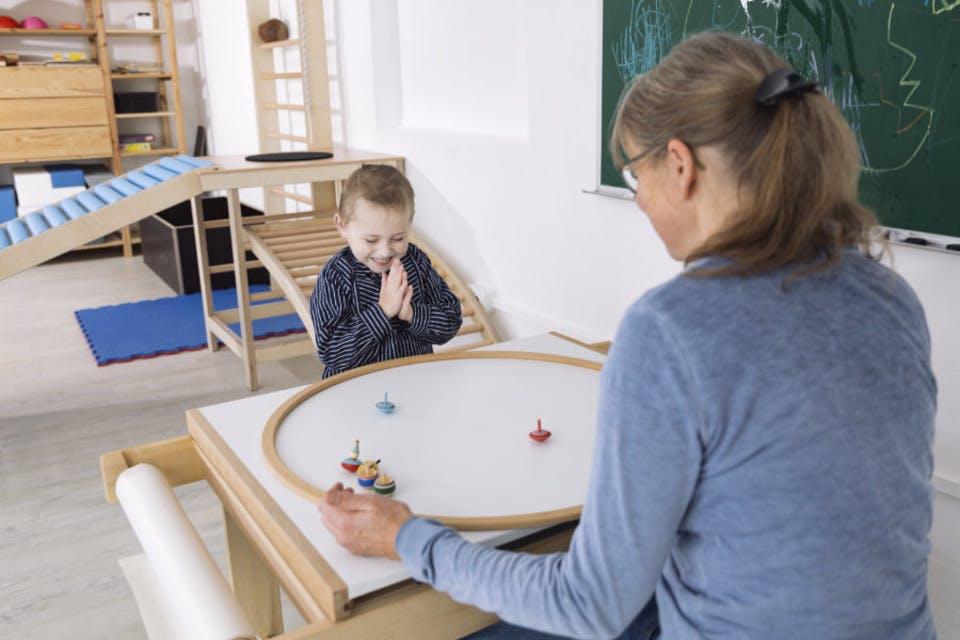 Ergotherapeutin sitzt mit Kind am Tisch und spielt Kreisel