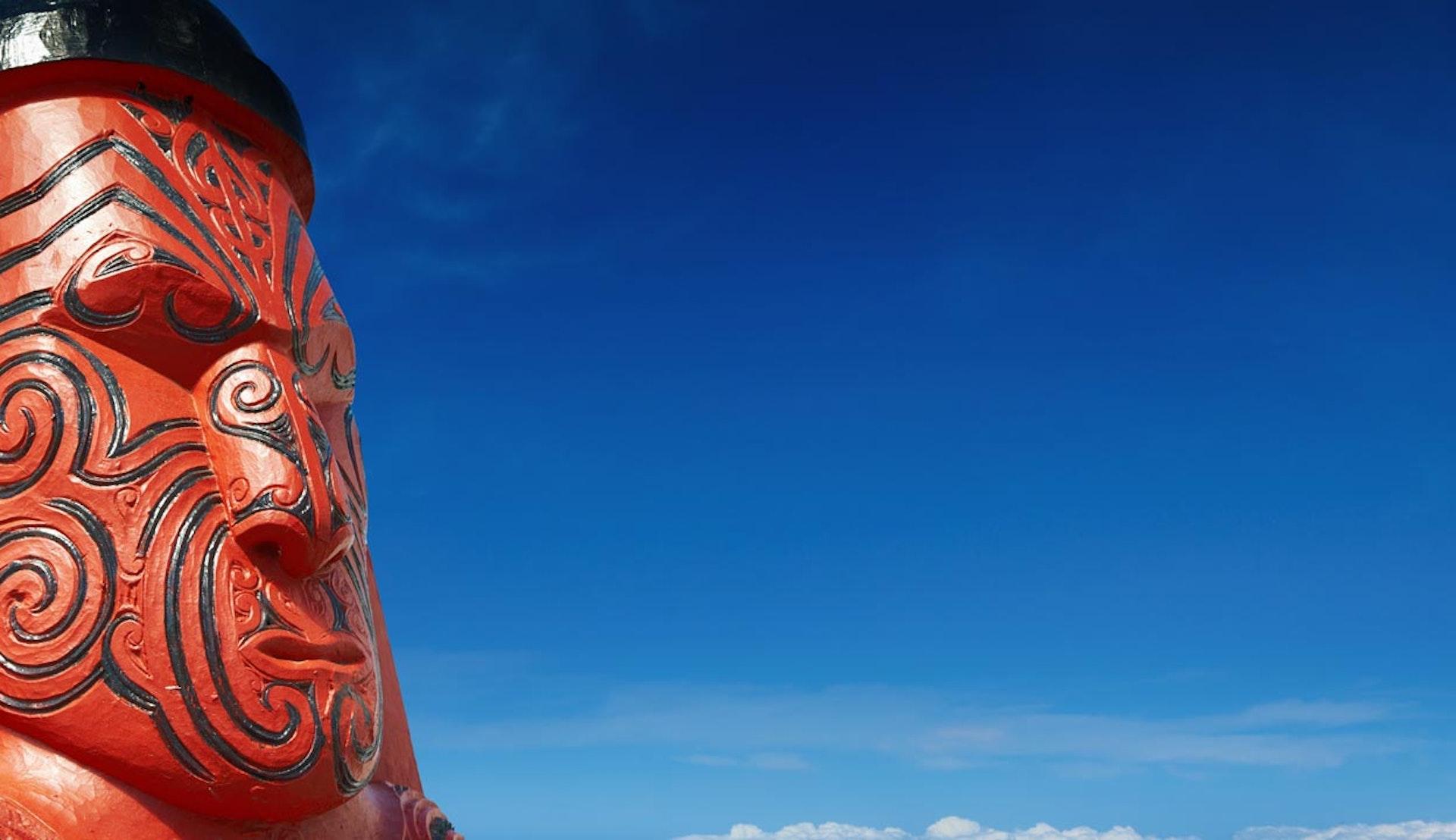 Röd och svart maoriskulptur från Nya Zeeland.