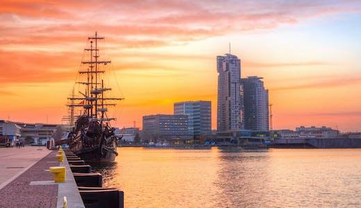 Solnedgång i Gdynia, Polen, med vackert skepp vid kajen.