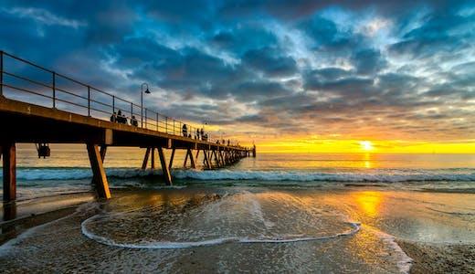 Solnedgång över Glenelg Jetty i Adelaide, Australien.