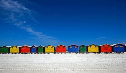 Färgglada små strandhus i Mossel Bay, Sydafrika.