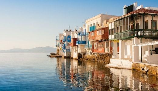 Grekiska hus precis vid vattnet, härligt badande i sol.