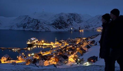 Par tittar ut över ett kvällsupplyst Honningsvåg i Norge. Foto: Ulrich Dajek/Hurtigruten
