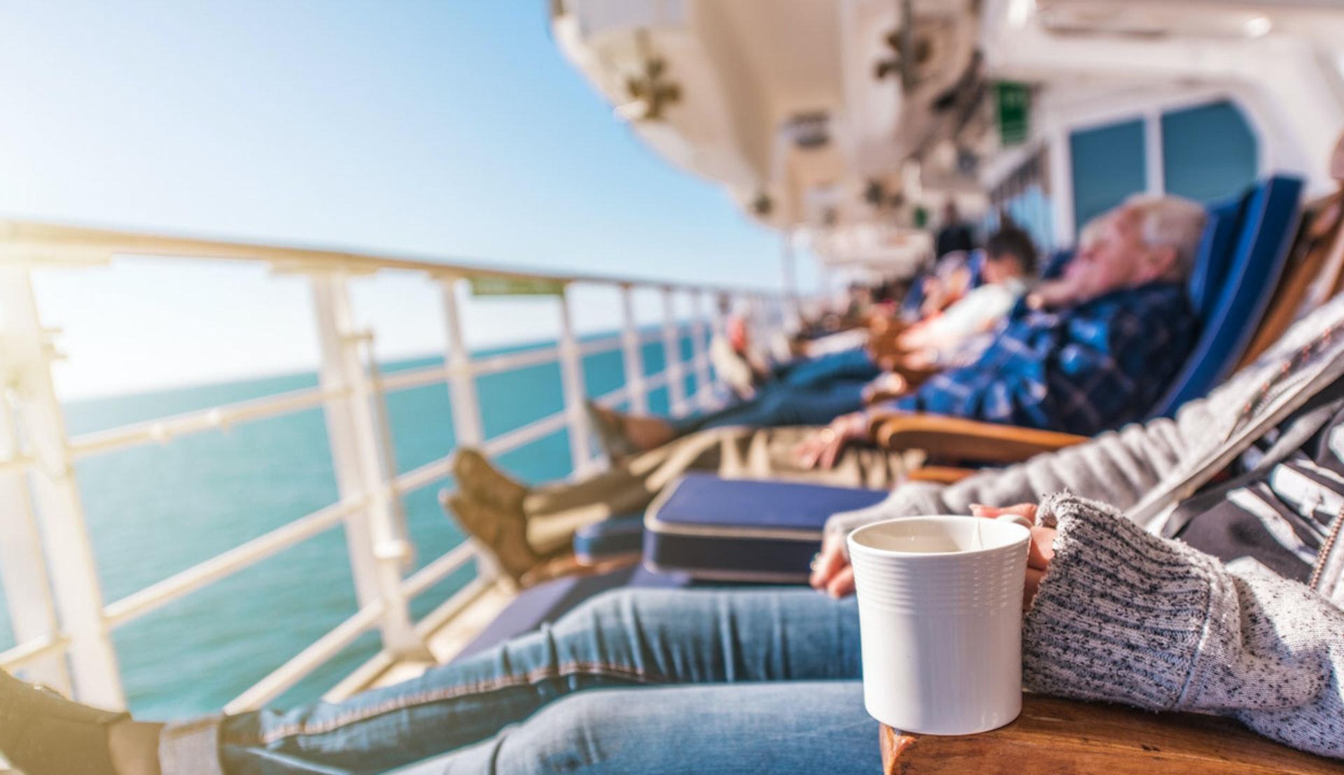Kryssningsresenärer som njuter i vilstolar på däck ombord.