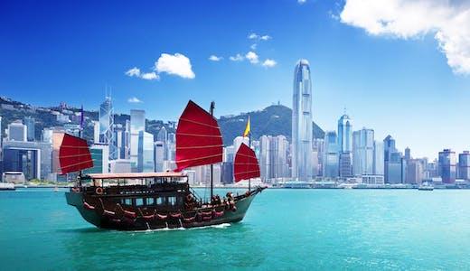 Vacker båt med röda segel, med Hongkongs skyline i bakgrunden.