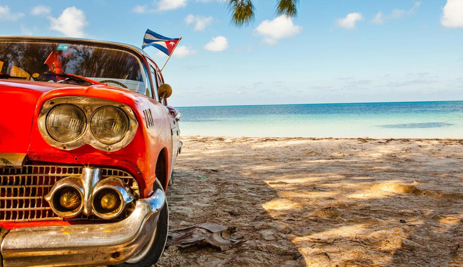 Röd bil med kubanska flaggan som vajar i vinden, på en strand.