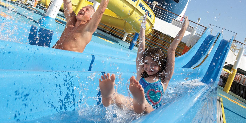 Pappa och dotter tävlar i vattenrutschbanorna på ett av Carnivals fartyg.