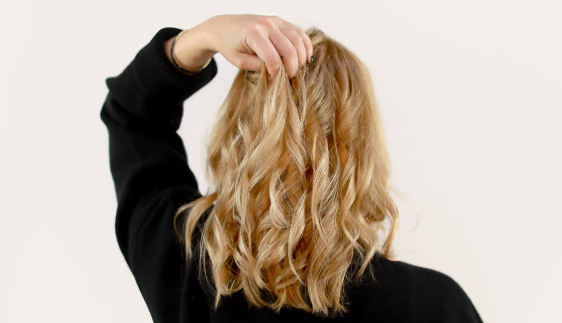 Image of back of head esalon client courtney with a custom buttery blonde hair color trending for fall