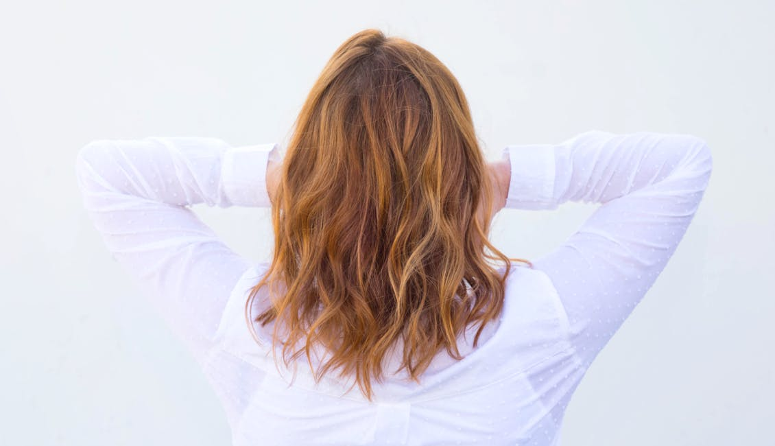 Image of esalon client back of head shot featuring trending custom hair color apple cider fireball with deep blonde copper color