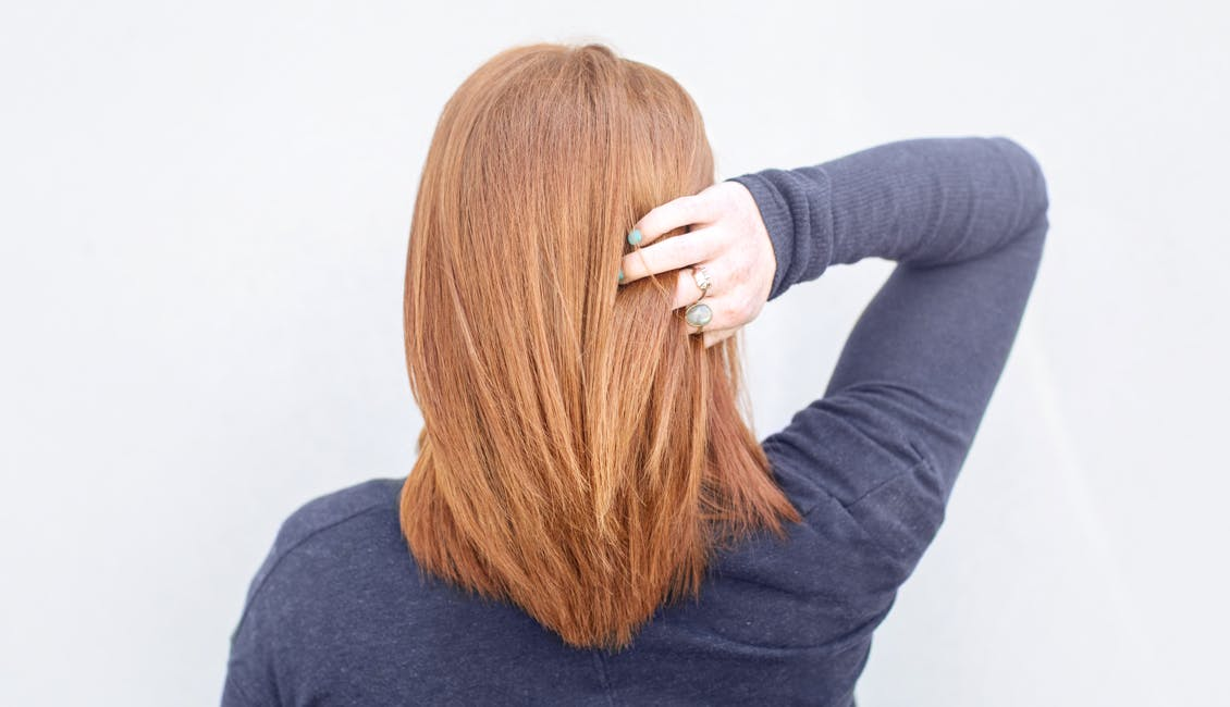 Image of esalon client with a burst of copper hair color featured in color mastery spring trends article
