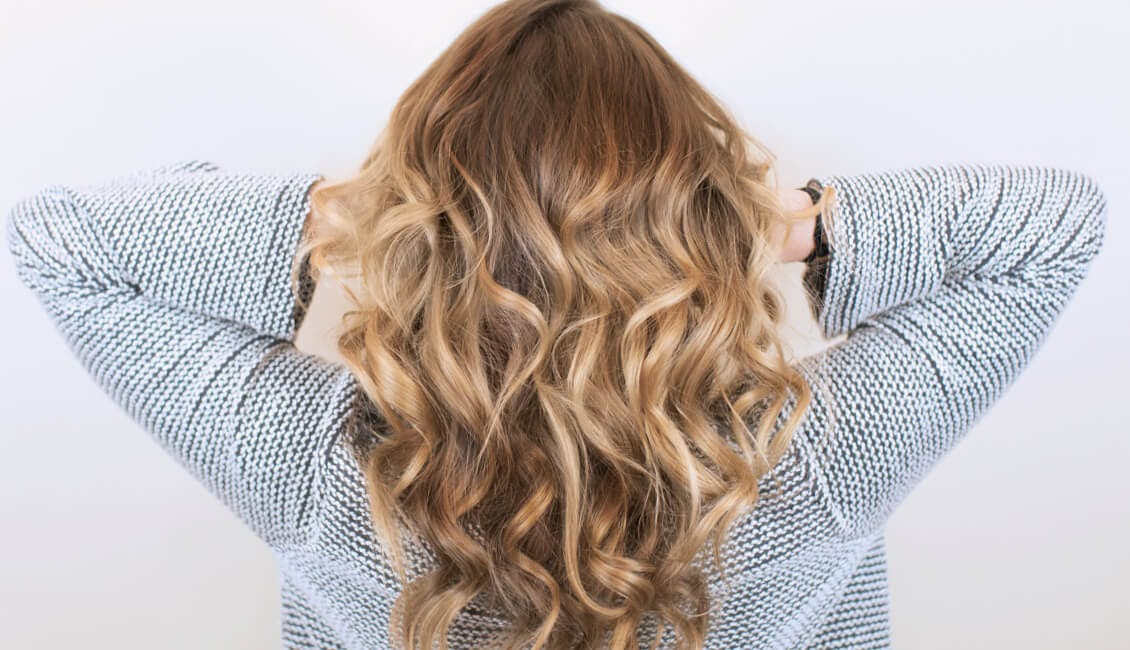 Image of esalon client back of head with custom toffee hair color and her hands in her curly hair