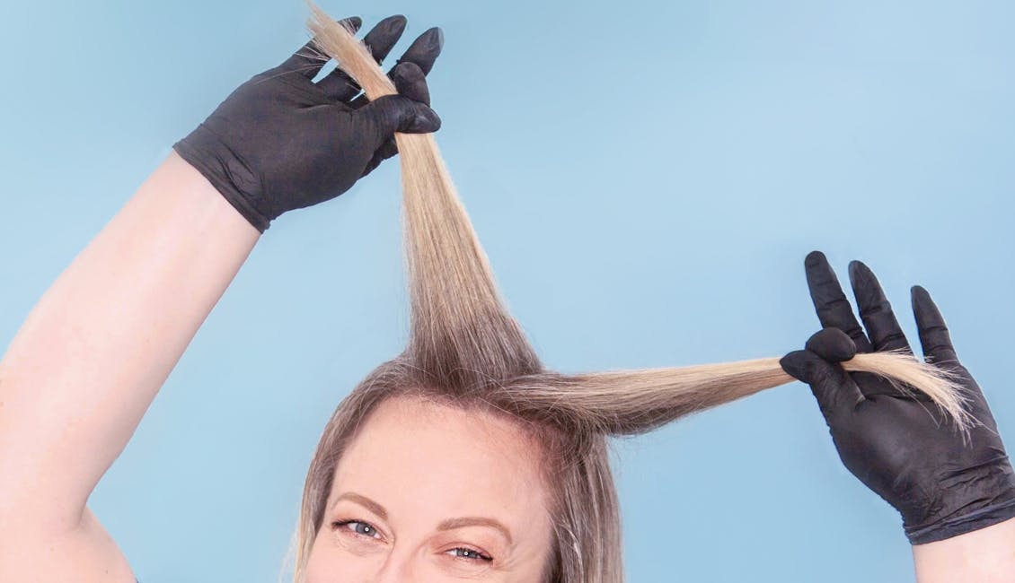 Image of esalon colorist separating her hair into sections before highlighting her side bangs with light set home balayage kit