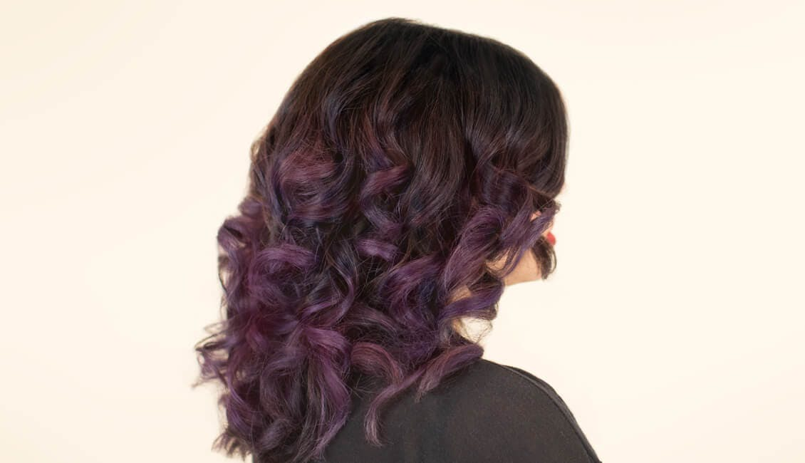 Image of esalon client with mulled wine custom hair color which has a dark base shade and purple ends