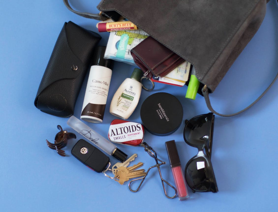 Image of esalon employee's dark handbag tipped over with esalons camo mist, sunglasses, lip gloss, eyelash curler, aveeno hand lotion, sunglasses case, burt's bees lip balm, dolce and gabbana perfume roller, and a hair clip