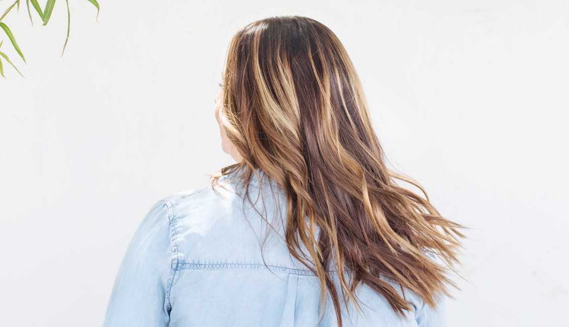 Image of esalon client with rooty roots hair color trending for spring