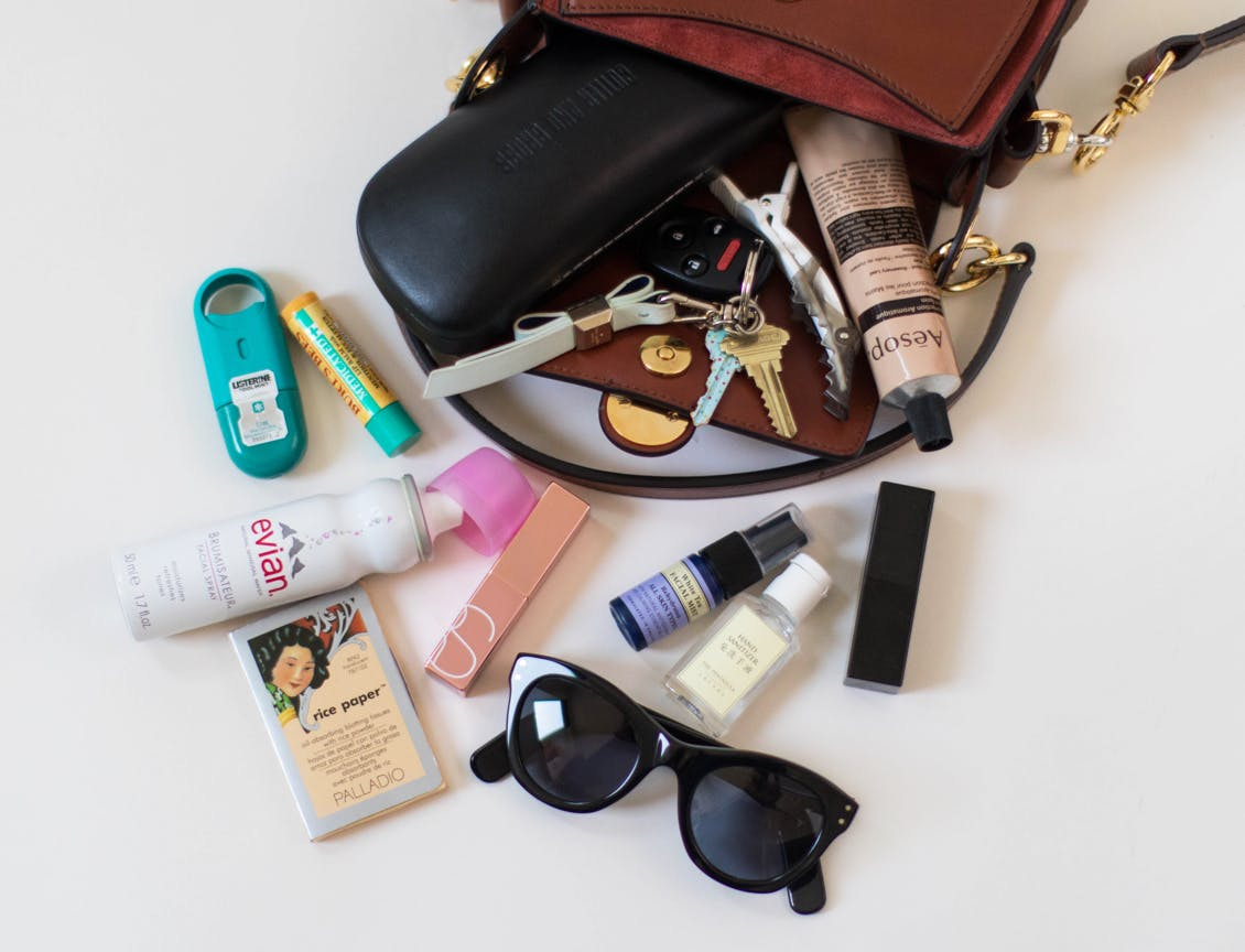 Image of esalon employee Jules' brown handbag spilled over with breath spray, evian facial spray, rice blotting papers, sunglasses, hand sanitizer, lipstick, perfume, burt's bees lip balm, aesop hand lotion tube and keys