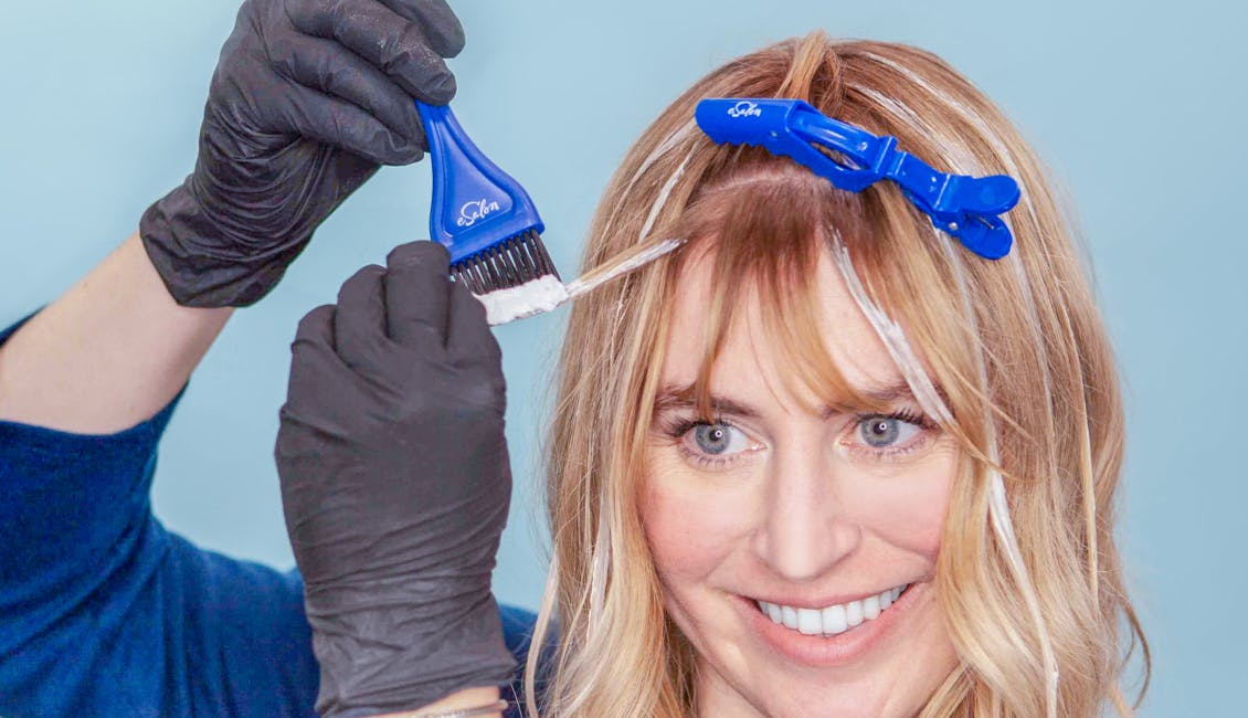 Image of easlon colorist highlighting her bangs with a tint brush and esalons light set home highlighting kit