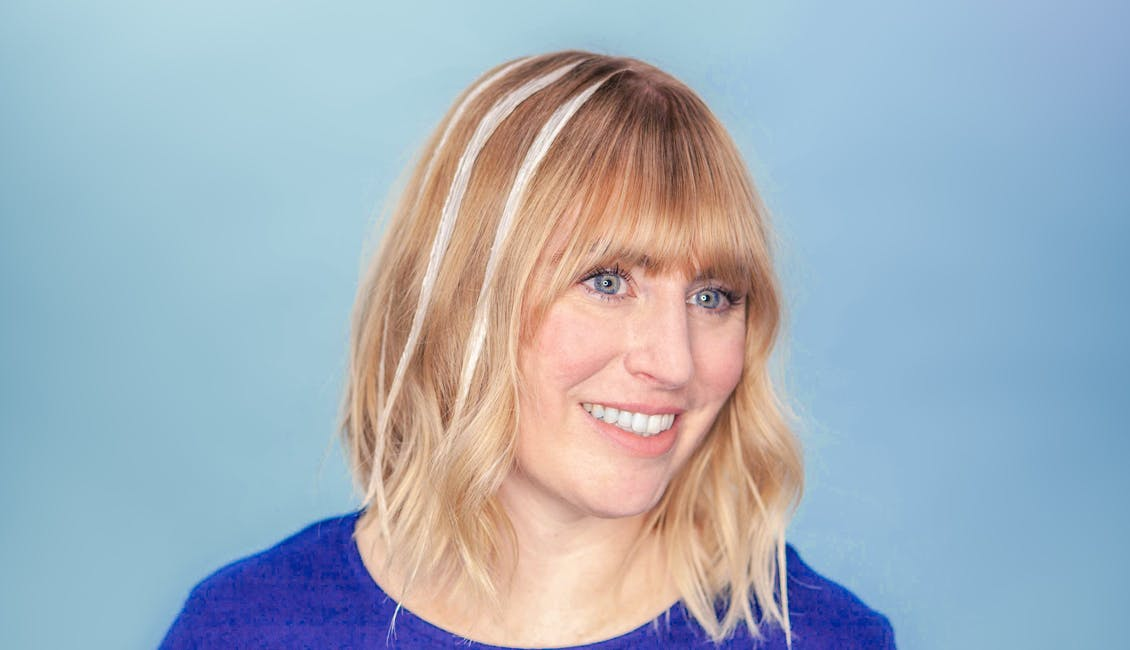 Image of colorist with strips of light set formula in hair to achieve balayage highlights at home with esalon